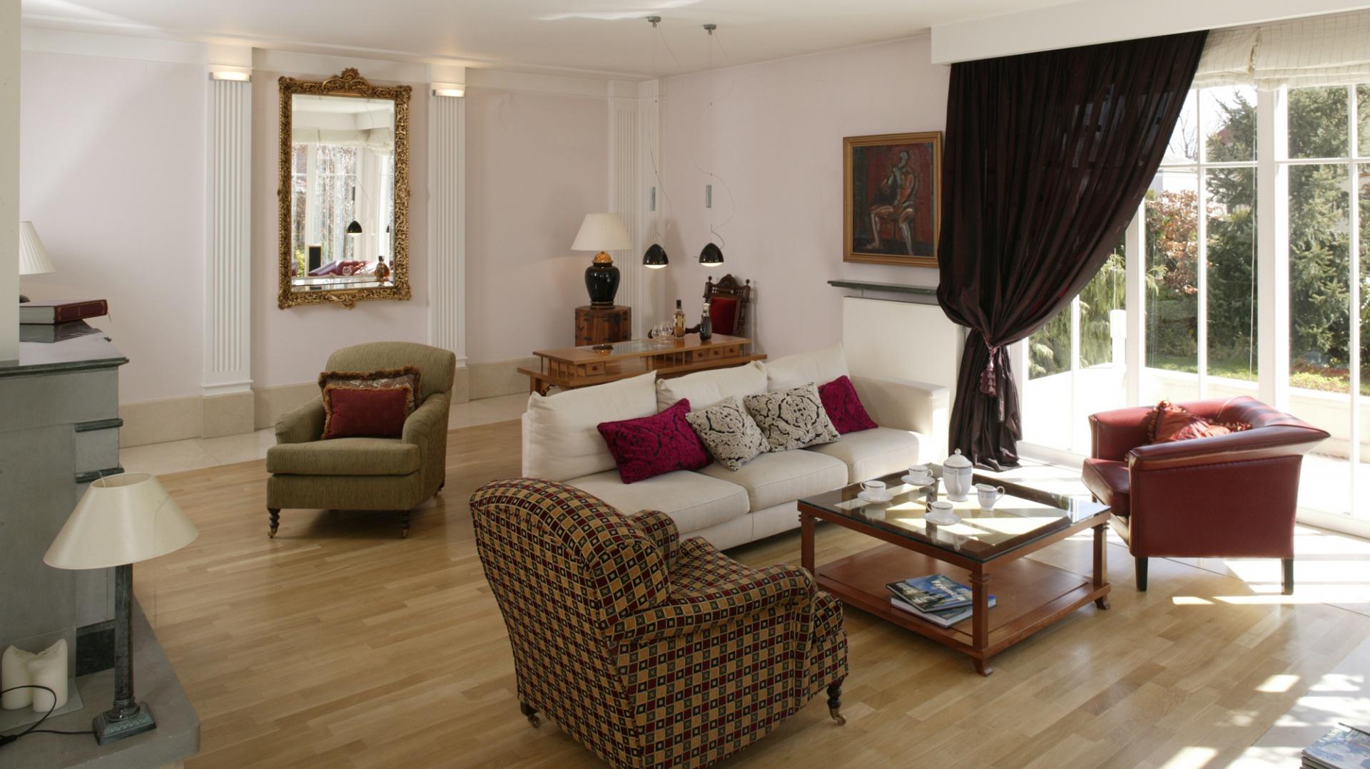 Francuskie fotele – każdy w innej tkaninie, biała kanapa, kotary i poduszki wprowadzają do salonu dużo ciepła i przytulności. Tkaniny były dobierane przez architekta i panią domu. Fot. Bartosz Jarosz.