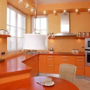 Soczyście pomarańczowa kuchnia. Meble wykonano na zamówienie, fronty szafek z mdf-u, blaty z lakierowanej na pomarańczowo sosny. Kolorystycznie dobrano do nich niewielkie płytki (Voque). Fot. Bartosz Jarosz.