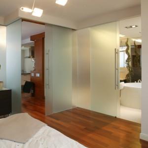 Wejście do sypialni stanowią rozsuwane drzwi. Całą ich konstrukcję mechaniczną, która znajduje się przy suficie, ukryto za wykonaną z czereśniowego drewna niszą. Fot. Tomasz Markowski.