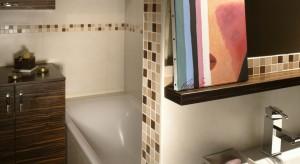 Nawet w niewielkiej łazience można podzielić przestrzeń na obszary bardziej i mniej intymne. Tutaj pomogła w tym ścianka, która przesłania wannę, a jednocześnie wydziela strefę dostępną gościom. Z lustra spogląda na nich życzliwe