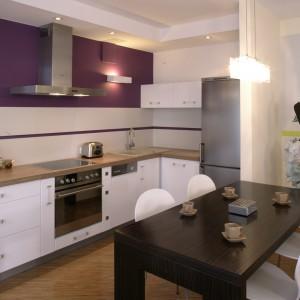 Część stricte kuchenna jest minimalistyczna, ale bardzo efektowna, głównie za sprawą mocnego koloru, którym pomalowano ścianę. Specjalnie zaprojektowane, proste meble zostały wykonane przez firmę BRW.
