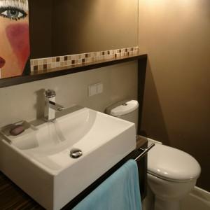 Przycupnięty w kącie sedes nie zakłóca artystycznego klimatu łazienki. Masywna bryła umywalki opiera się  na prostopadłościennej szafce z relingiem na ręcznik. Fot. Monika Filipiuk.