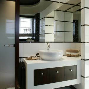Umywalka (o zaokrąglonym jak cała ceramika kształcie) została oparta na białej szafce z kompozytu, wyposażonej w drzwiczki w kolorze wengé. Fot. Monika Filipiuk.
