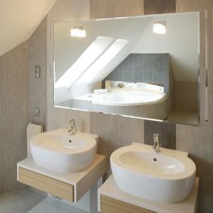 W niewielkich, montowanych do ściany, szafkach pod umywalkami znajdują się bezuchwytowe szuflady. Lampy zainstalowane bezpośrednio na lustrze sprawiają, jakby świeciło ono własnym światłem. Fot. Monika Filipiuk.