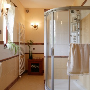 Kabina z panelem prysznicowo-masażowy jest ustawiona przy dobudowanej ściance. Mała szafka na zapasowe ręczniki to także stylowa dekoracja łazienki.  Fot. Monika Filipiuk.