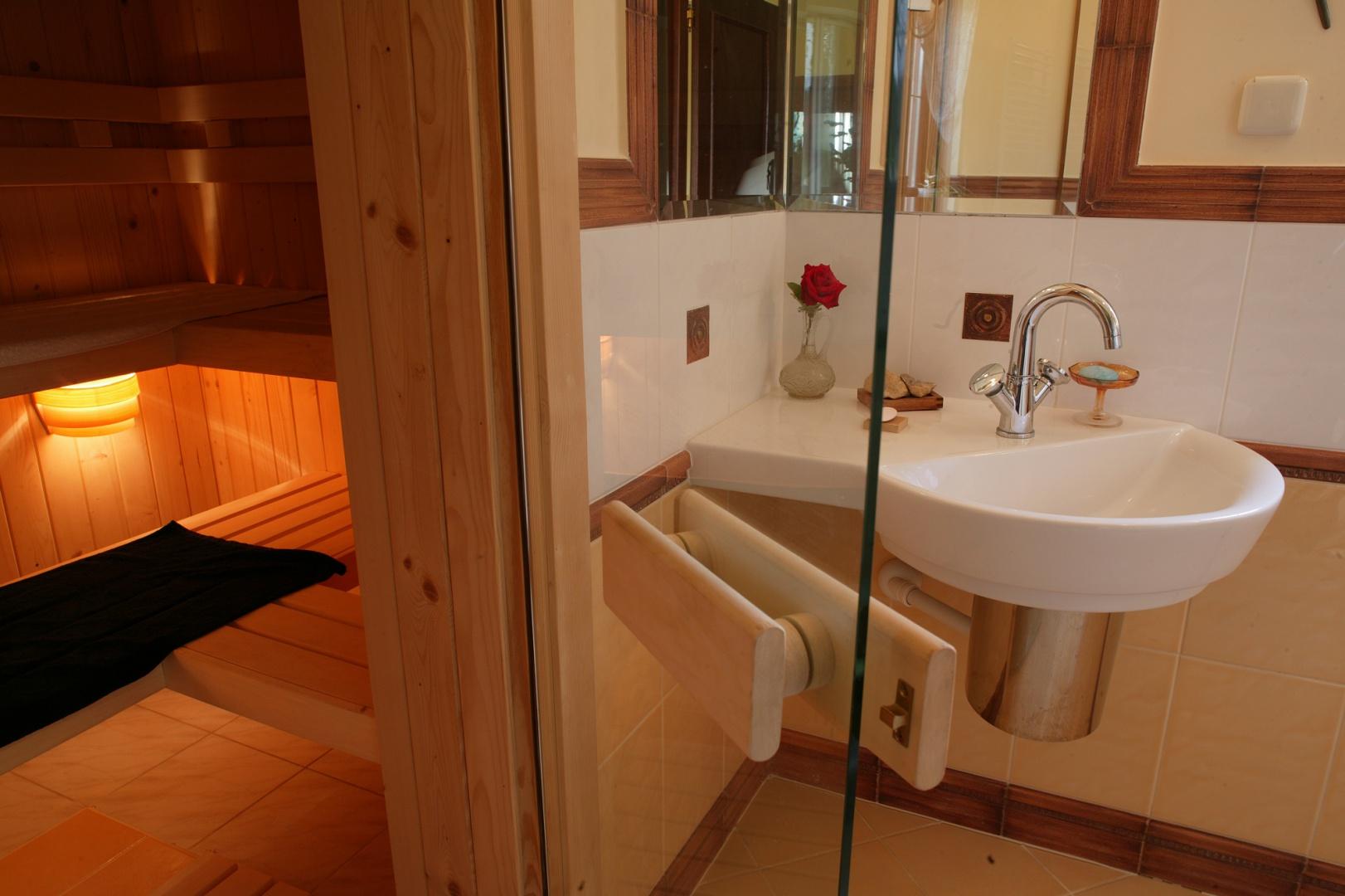Na ławkach w saunie można oddawać się kąpieli leżąc lub siedząc. Nastrojowe światło lamp i szklane drzwi dają poczucie większej przestrzeni.  Fot. Monika Filipiuk.