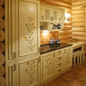 Drewniane fronty mebli o beżowo-żółtawym odcieniu zdobią ręcznie malowane wizerunki dziurawca. Stojące szafki przykrywa blat roboczy z egzotycznego kamienia. Fot. Bartosz Jarosz.
