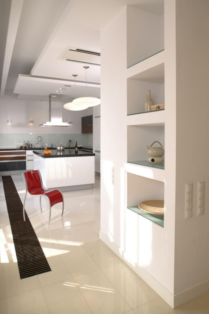 Czerwone, designerskie krzesło (Kartell), to jeden z nielicznych barwnych akcentów w kuchni, szczególnie widoczny na tak stonowanym tle. Fot. Monika Filipiuk.