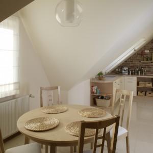 Jadalniany komplet – okrągły stół i wysokie krzesła - stanowi umowną granicę między przestrzeniami kuchni i salonu, bardziej jednak je integrując, niż dzieląc. Fot. Monika Filipiuk.