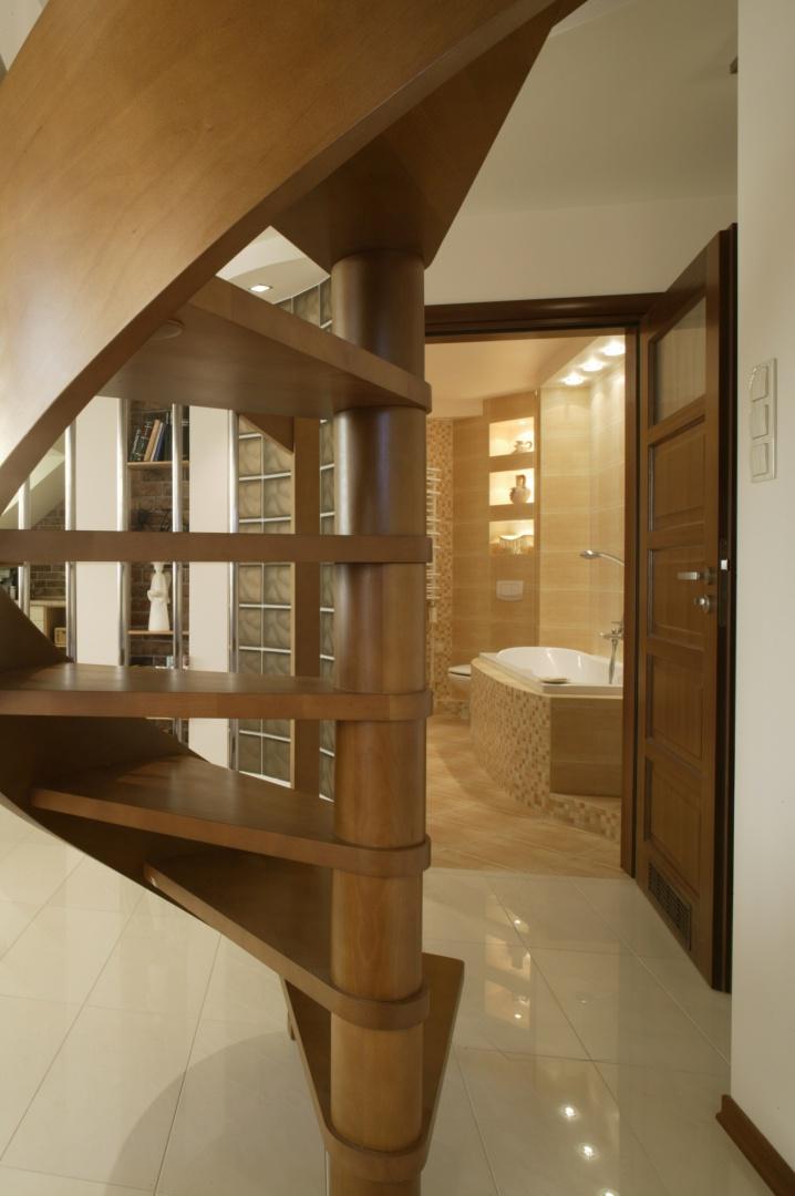 Rzeźbiarska konstrukcja, widoczna w holu tuż przy wejściu do łazienki to nic innego, jak... schody na antresolę. Wraz z łukowatą ścianą z pustaków szklanych tworzą intrygującą przestrzenną kompozycję. Fot. Monika Filipiuk.