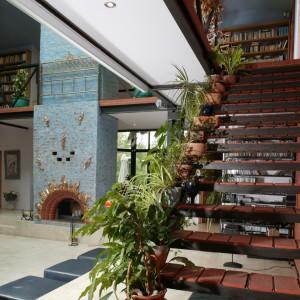 Na pierwszym planie: schody do książek i kwietny wieniec. W tle: dusza salonu, czyli niebiesko-złoty, słoneczny kominek. Fot. Tomasz Markowski.