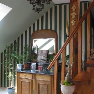 Jedna ze ścian w salonie została pokryta tapetą w pionowe, zielono-beżowe pasy. Wraz z towarzysząca jej starodawną toaletką wprowadza do mieszkania klimat rodem z dziewiętnastowiecznych angielskich domostw. Fot. Tomek Markowski.