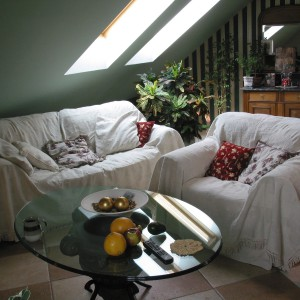 Komplet wypoczynkowy został przykryty beżowymi narzutami i wymoszczony miękkimi poduszkami. W ten sposób powstała doskonała strefa relaksu, która w zależności od potrzeby szybko przemienia się w kącik kawowy. Fot. Tomek Markowski.