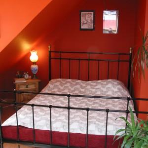 Łóżko w sypialni zostało ulokowane w przytulnym zakątku, który zdaje się kumulować wszelką pozytywną energię. Ściany pomalowane na soczysty kolor pomarańczy są jednym z podstawowych elementów określających tropikalny charakter tego miejsca. Fot. Tomek Markowski.