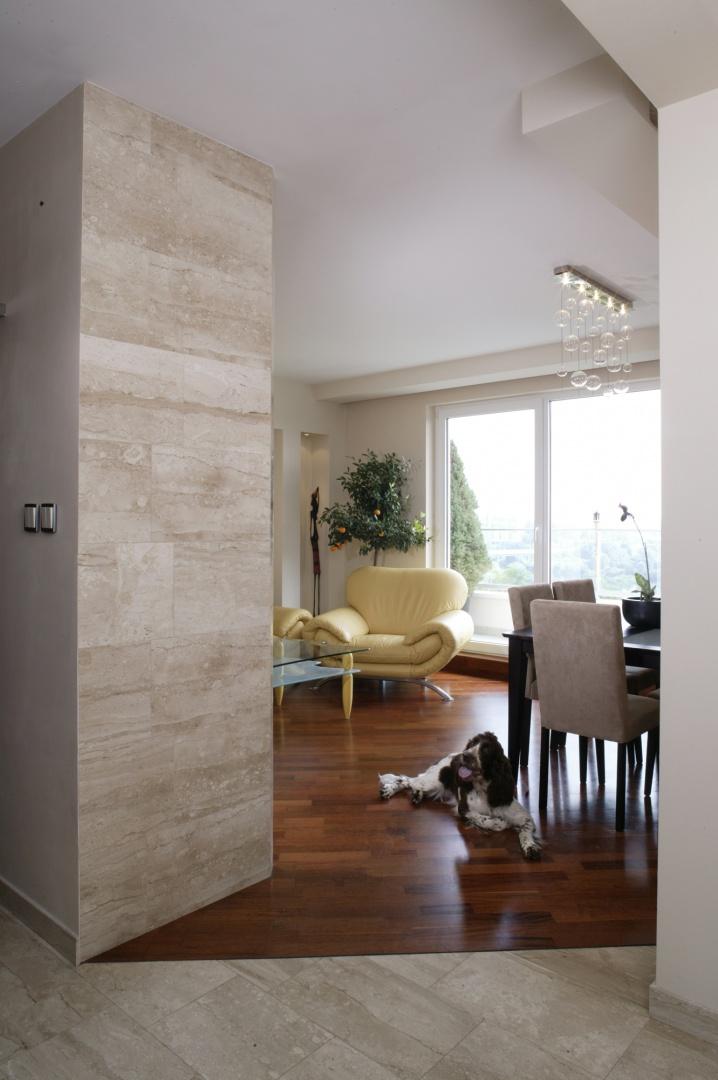 Ścianka u wejścia do salonu została dobudowana pod odpowiednim kątem, by z sofy można było wygodnie oglądać program telewizyjny. Pokryta jest jasnymi płytkami z marmuru (Travertino Marfil), które pojawiają się również na podłodze w kuchni i holu. Fot. Monika Filipiuk.