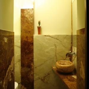 Onyks w jasnych odcieniach został zestawiony w łazience dla gości z ciemnym trawertynem. Jego niezwykłą krystaliczną strukturę dodatkowo podkreśla oświetlenie. Fot. Bartosz Jarosz.
