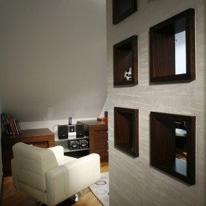 Ażurowe półki, łóżko w specjalnie dla niego stworzonej niszy, biały, duży fotel i do tego dywan, o stonowanych barwach i z geometrycznym wzorem. Po prostu wnętrze wymagającego podróżnika. Fot. Monika Filipiuk.