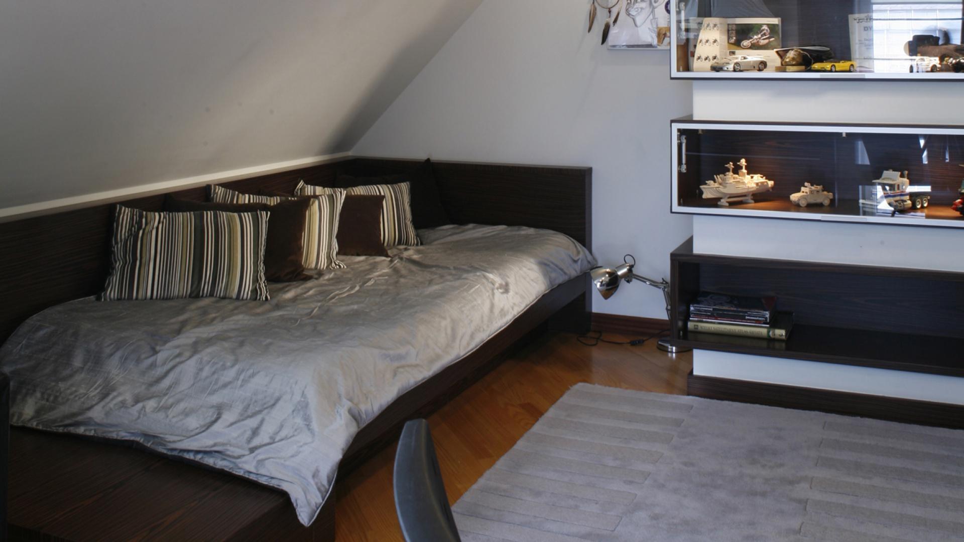 Zabudowane z dwóch stron łóżko, idealnie wpasowano pod skośną ścianę. Dzięki odpowiedniemu oświetleniu, miejsce to wieczorami zmienia się w kącik do czytania. Fot. Monika Filipiuk.