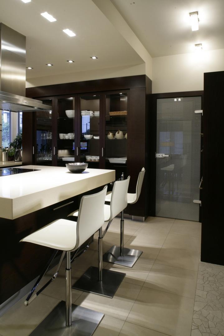 Bezpośrednio z kuchni wchodzi się do spiżarni. Oba pomieszczenia oddzielają drzwi ze szkła z maskującym, geometrycznym nadrukiem. Fot. Bartosz Jarosz.