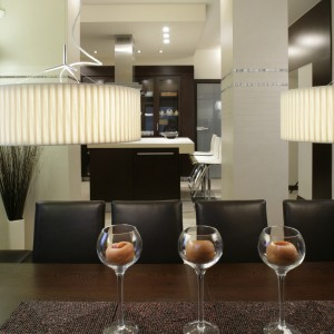 Jadalnia i kuchnia znajdują się w reprezentacyjnej części domu. Ich wystrój jest nowoczesny, lecz z dozą eleganckiej przytulności. Ten klimat współtworzy precyzyjnie zaprojektowane oświetlenie. Fot. Monika Filipiuk.