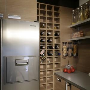 Regał na ok. 50 butelek wina oraz pozostałe szafki są wykonane z jasnej płyty meblowej. Dla kontrastu, nawiązującego do dalszej części domu, sufit pomalowano na czekoladowy kolor. Fot. Monika Filipiuk.