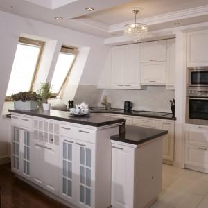 Wyższa szafka barowa tworzy z kuchennym półwyspem jedną bryłę. Za dnia kuchnię oświetlają połaciowe okna, wieczorem halogeny i kryształowe żyrandole. Fot. Monika Filipiuk.