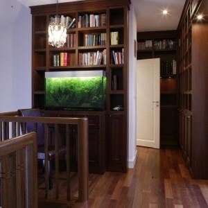 Antresola mieszkania to wielka biblioteka. Regały z drewna merbau i akwarium są widoczne z usytuowanego piętro niżej salonu. Białe drzwi prowadzą do dziewczęcej łazienki. Fot. Monika Filipiuk.