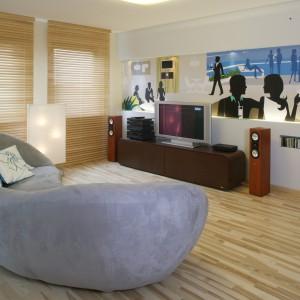 W dużym, otwartym salonie prym wiedzie barwna ścienna grafika i wielka sofa o organicznym kształcie (MebelPlast). Jasna podłoga z drewna jesionowego i drewniane żaluzje w podobnym odcieniu, stanowią dla nich stonowane tło. Fot. Monika Filipiuk.