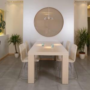 Dekoracyjną ściankę z bulajem (łączącym jadalnię z łazienką) pokryto srebrną tapetą, idealnie komponującą się z hi-techową lampą nad stołem (IKEA) i szarymi płytkami podłogowymi. Przy ściance stanął solidny, jasny stół oraz obite pluszem, krzesła na aluminiowych nóżkach (Noti). Fot. Monika Filipiuk.
