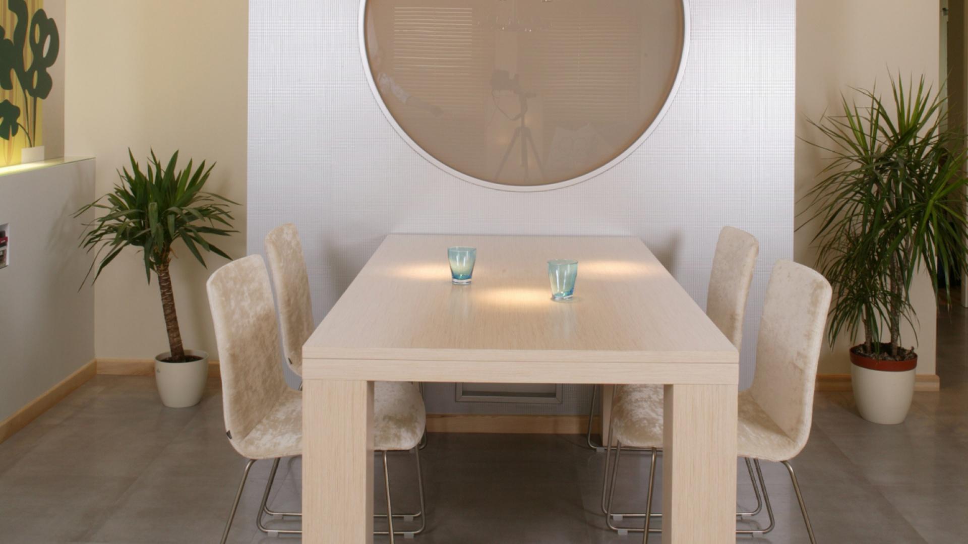 Srebrna tapeta, która pojawia się w kuchni, została również wykorzystana na dekoracyjnej ściance z bulajem. Doskonale harmonizuje z hi-techową wiszącą lampą (Ikea). Monika Filipiuk.