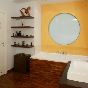 Drugą stronę ściany z bulajem można obejrzeć od strony łazienki, która została pomalowana na energetyczny pomarańczowy kolor. Barwa ta kontrastuje z ciemną podłogą i obudową wanny z drewna merbau. Monika Filipiuk.