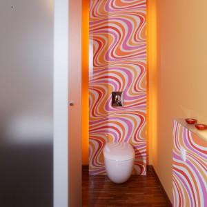 Malutka, ale jakże dynamiczna toaleta. Sedes został zawieszony na ściance pokrytej optymistycznym wzorem z falistych kolorowych linii i podświetlonej od tyłu świetlówkami. Monika Filipiuk.