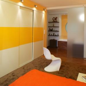 Pomarańcz, wzorzysta tapeta – tyle wystarczy, by stworzyć tło dla wyeksponowanych na podświetlanej od dołu szklanej półce, kolorowych drobiazgów ze szkła i pleksi (Flo). Monika Filipiuk.