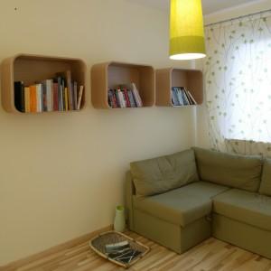 Zawieszone na ścianie półki mają oryginalny kształt. Barwa drewnianych, pozbawionych kantów mebli, doskonale koresponduje z wybarwieniem podłogi. Fot. Monika Filipiuk.