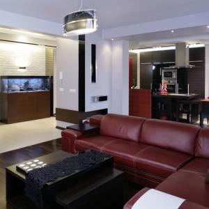 Z salonu doskonale widać kolorystyczną konsekwencję całej aranżacji: czerwona kanapa, parkiet z egzotycznego palisandru i pomalowana na szaro ściana wyznaczają podstawową paletę kolorów. Fot. Monika Filipiuk.