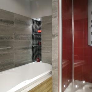 Szklane elementy (stojące pionowe szafki na łazienkowe drobiazgi, szklane półki we wnęce) oraz lustro – optycznie powiększają niewielką łazienkę. Fot. Monika Filipiuk.