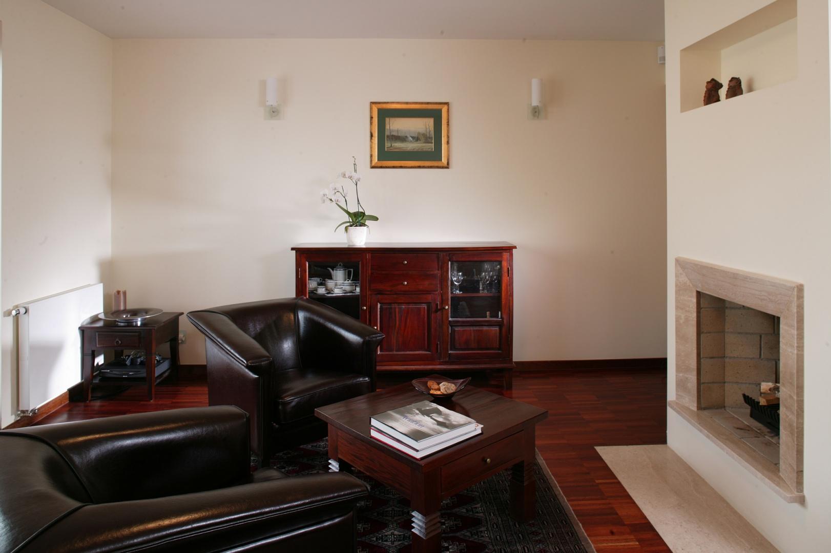 Salon górny spełnia funkcje reprezentacyjne. Kominek nie jest zbyt dekoracyjny, natomiast meble - tapicerowane skórą fotele oraz stylowa komoda i narożny stolik - wprowadzają do wnętrza oficjalny ton. Fot. Tomek Markowski.