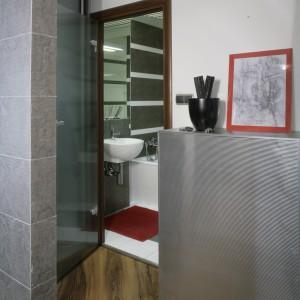 Przy drzwiach do łazienki umiejscowiono szafkę-podest, obitą PCV imitującym blachę. To kolejny przykład na łączenie funkcji użytkowych i dekoracyjnych. Fot. Monika Filipiuk.
