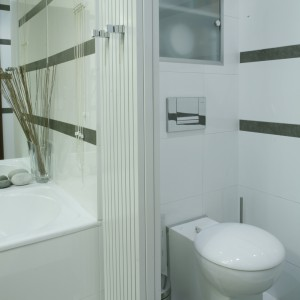 Lśniące powierzchnie, lustra i szkło to zabiegi, które zawsze optycznie powiększają przestrzeń łazienki. Fot. Monika Filipiuk.