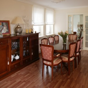 Z salonu przechodzi się wprost do jadalni, gdzie honorowe miejsce zajmują stylizowane meble – ciemnobrązowy, rozkładany stół z krzesłami w tym samym kolorze i piękny kredens. Fot. Markowski Tomek.