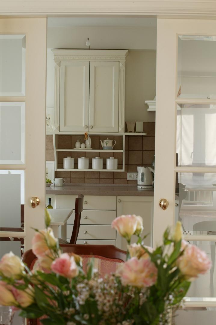 Pierwszy plan jadalni tworzą włoskie meble – owalny stół z szeregiem obitych oryginalną tapicerką krzeseł. Kwiaty są codziennym elementem wystroju. Fot. Tomasz Markowski.