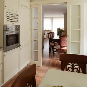 Dzielące kuchnię i jadalnię przesuwane drzwi wtapiają się w ich wystrój. Swoją formą i kolorystyką podkreślają zwarty układ kuchennych mebli. Fot. Tomasz Markowski.