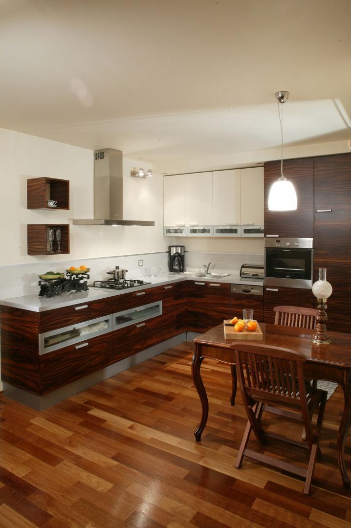 Nowoczesna kuchnia ubrana w egzotyczne drewno nie tylko wtapia się w stylowo urządzony salon, ale też stanowi dogodne tło do wyeksponowania starego stołu i współczesnych krzeseł w stylu kolonialnym. Fot. Tomasz Markowski.