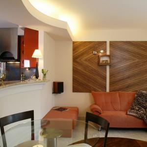 Mocnymi akcentami gościnnego pokoju są pomarańczowy, narożny wypoczynek z dużą pufą oraz blaty drewna zebrano, umieszczone na ścianie. Zaokrąglony blat barowy łączy salon z kuchnią. Fot. Marcin Łukaszewicz.