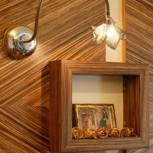 """Na ścianie z """"boazerią"""" została umieszczona mała ramka, w której powstał rodzaj ołtarzyka z reprodukcją Giotta z Asyżu i zasuszonymi różami. Całość podświetla metalowa lampka z kwiatowym, secesyjnym kloszem. Fot. Marcin Łukaszewicz."""