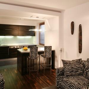 Jasne ściany salonu pięknie kontrastują z ciemnobrązowymi tonacjami mebli, podłóg i zabudowy aneksu kuchennego, wydobywając w ten sposób oryginalne afrykańskie maski, etniczne dekoracje i suche kompozycje z gałęzi. Fot. Tomasz Markowski.