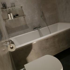 Wszystkie ściany oraz zabudowę wanny w łazience wykończono stiukiem o fakturze mokrego betonu. Następnie na ich powierzchnie nałożono specjalną warstwę wosku, która powoduje, że ściany są wodoszczelne i można je myć, jak np. płytki ceramiczne. Fot. Tomasz Markowski.