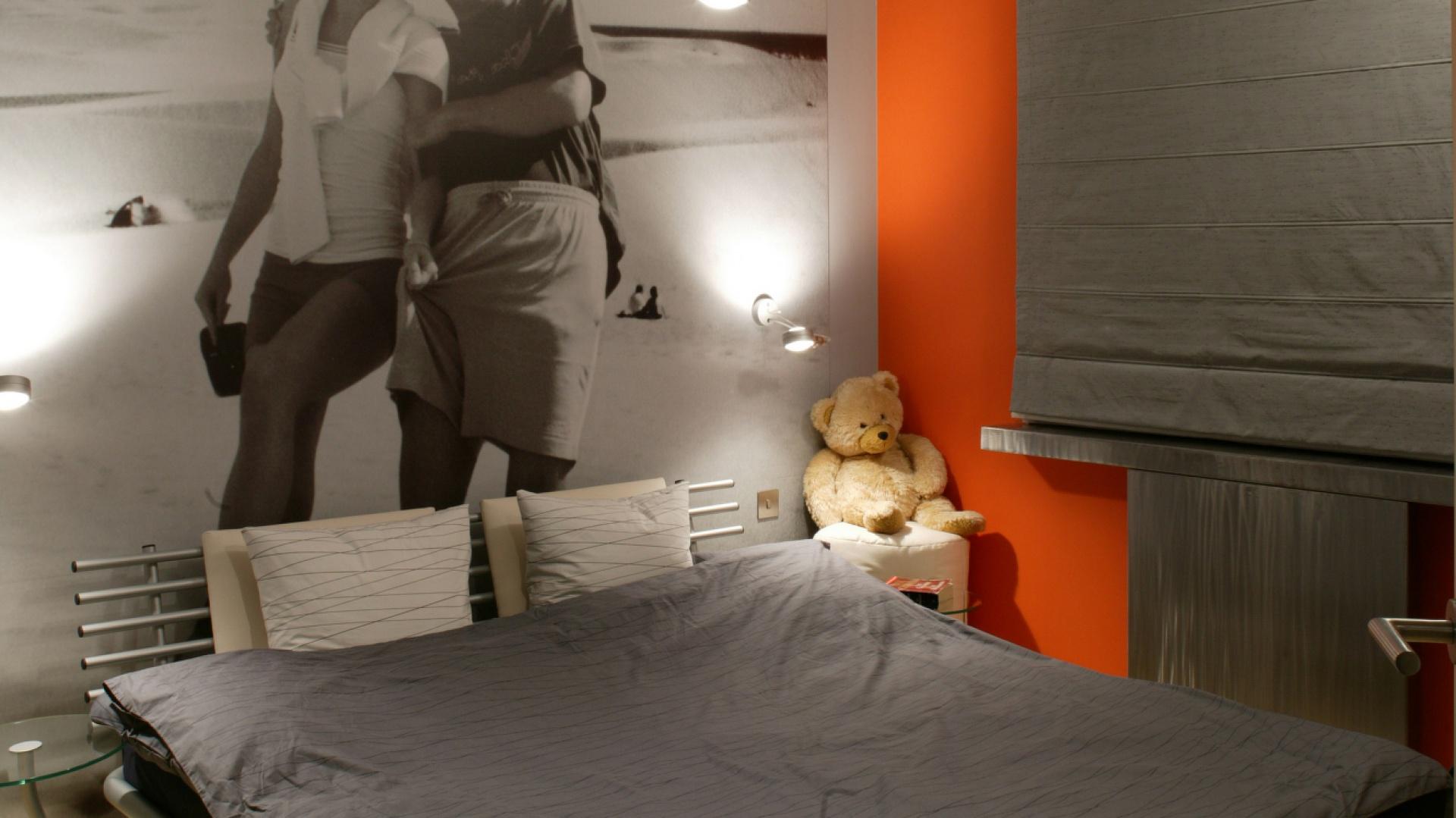 Dwie dominanty zawładnęły sypialnią: powiększone do maksimum, czarno-białe, wakacyjne zdjęcie gospodarzy oraz pomarańczowa ściana – jedyny kolorowy akcent we wnętrzu. Fot. Tomek Markowski.