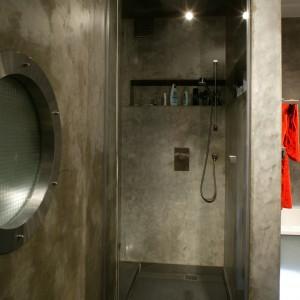 Utworzona we wnęce kabina prysznicowa znajduje się na wprost wejścia. Wyposażona jest w tradycyjny natrysk,  głowicę deszczową w suficie i wymodelowaną w ścianie półkę. Fot. Tomasz Markowski.