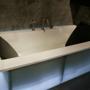 """Czarne zagłówki zapewniają wygodę w kąpieli, są też znakiem rozpoznawczym wanny """"Zero"""" marki Hoesch. Światło z - umieszczonej za szklaną obudową - świetlówki spowija ją niebieskawą poświatą. Fot. Tomasz Markowski."""